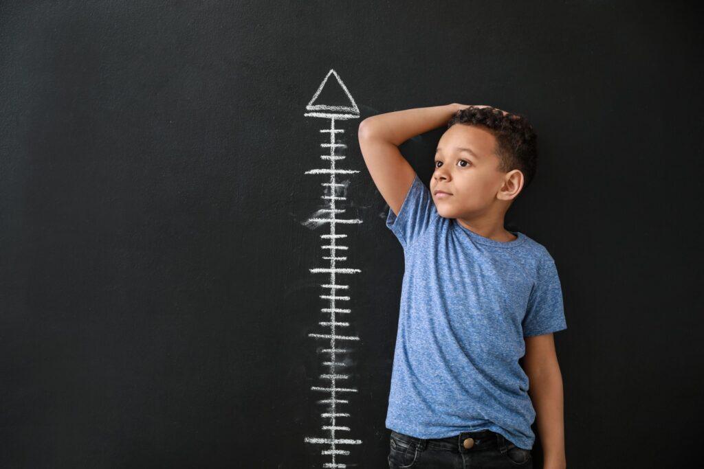 little boy measuring himself against scale on blackboard