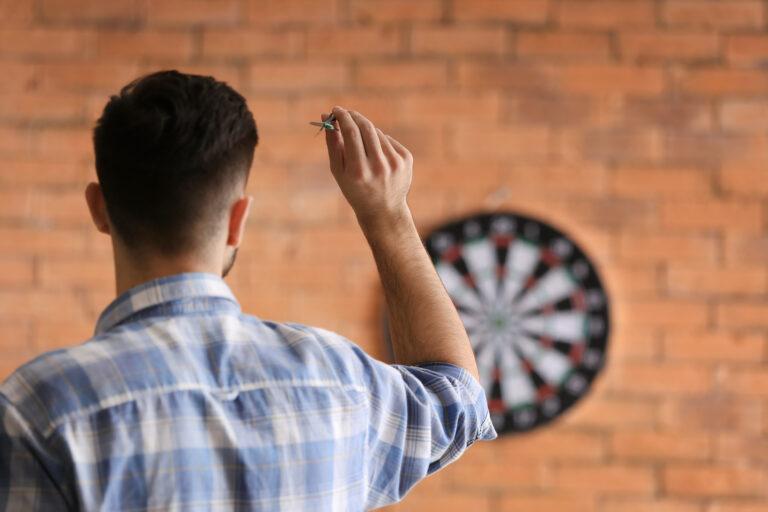 Man throwing dart as analogy for goal setting